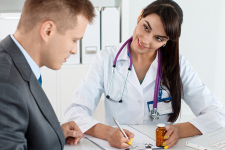 medical cure: Beautiful female medicine doctor giving to male patient in business suit jar of pills. Antidepressant or man sexual potency cure. Medical and pharmacy concept. Businessman visiting therapeutist