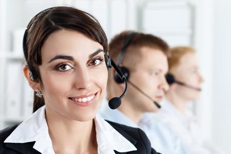 recepcionista: Tres llamadas operadores de servicios de centro en el trabajo. Retrato de la sonrisa de los empleados helpdesk hembra bonita con auriculares en lugar de trabajo. Informaci�n empresarial eficaz y eficiente, ayuda y apoyo concepto