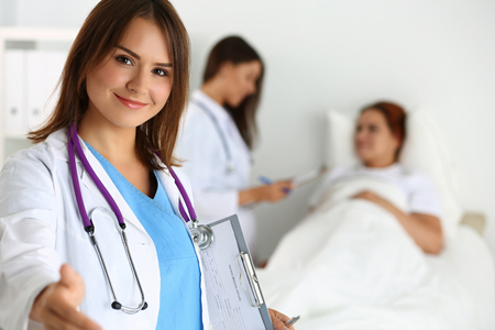 medical cure: Female medicine doctor offering hand to shake while patient lying in bed communicating with doctor during ward round. Greeting and welcoming gesture. Medical cure and tests advertisement concept Stock Photo