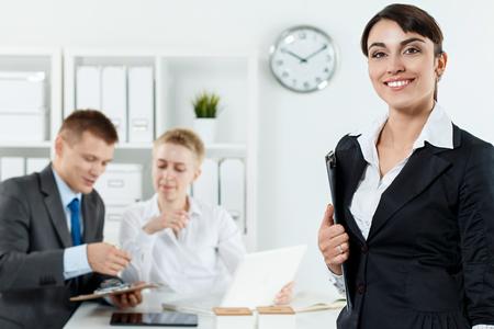 empleados trabajando: Hermosa mujer de negocios sonriente en traje de la celebración de portapapeles en las manos mientras que los empleados de pareja trabaja en segundo plano. Un negocio serio y la asociación, conferencias, oferta de trabajo, el concepto de éxito financiero