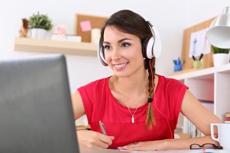 oir: Hermosa estudiante sonriente mujer usando el servicio de la educación en línea. Mujer joven que mira en la pantalla del portátil viendo curso de formación y escuchar con auriculares. Concepto de la tecnología de estudio moderno
