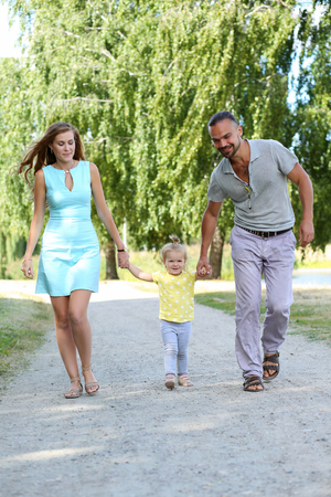 upbringing: Happy parents with daughter outdoor holding her hands. Beautiful smiling woman and handsome man walking with cute little girl in city park. Childhood and parenthood, baby care and upbringing concept
