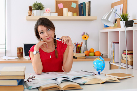 self development: Female student at workplace with pile of textbooks portrait holding pen studying. Woman writing letter, list, plan, making notes, doing homework. Education, self development and perfection concept Stock Photo