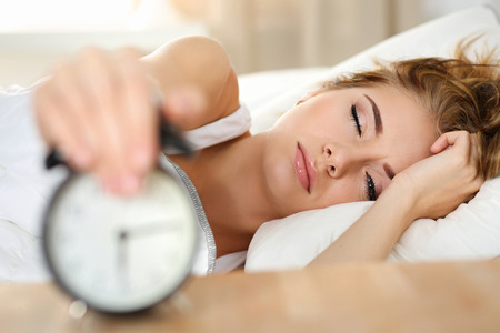 early morning: Sleepy young woman portrait with one opened eye trying kill alarm clock. Early wake up, not getting enough sleep, going work concept. Female stretching hand to ringing alarm willing turn it off Stock Photo