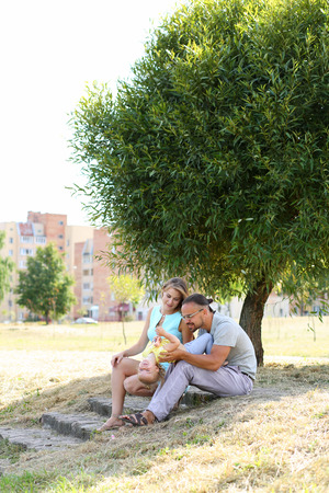 upbringing: Happy parents playing with daughter outdoor. Beautiful smiling woman and handsome man spending time with cute little girl in city park. Childhood and parenthood, baby care and upbringing concept
