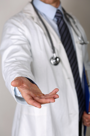 medics: Male medicine doctor offering helping hand closeup. Friendly and cheerful gesture. Medical cure and tests advertisement concept. Physician ready to examine and save patient