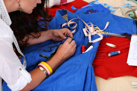 needlewoman: Female fashion designer sewing accessories to blue retro style dress with needle and threads. Creating garment, clothes sewing and repair service, seamstress at work in workshop concept