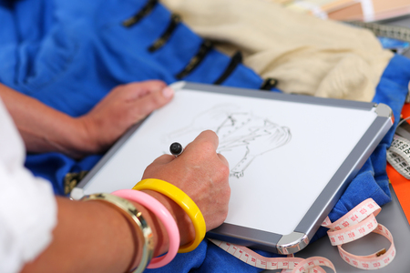 drawing pad: Female fashion designer hands holding drawing pad and pen making sketch of new dress. Style and design development and creating garment, clothes sew and repair service, seamstress at work concept