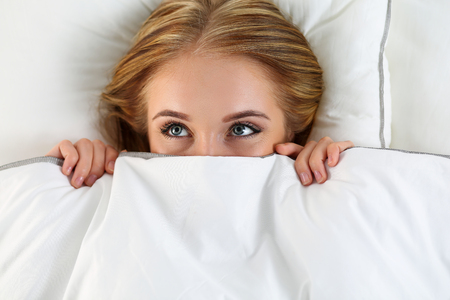 sex on bed: Beautiful blonde woman hiding face under cover lying in bed. Female sparky eyes looking up closeup. Sweet dreams, flirtation, playing game, wake up in strange place, shame, casual sex concept Stock Photo