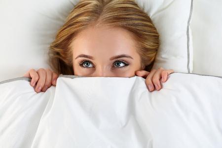 seks: Mooie blonde vrouw verbergt gezicht onder dekking in bed liggen. Vrouw Sparky ogen kijken omhoog close-up. Sweet dreams, flirt, playing game, wakker in vreemde plaats, schande, casual sex-concept