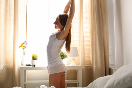 Joven y bella mujer de pelo largo sonriendo levantarse temprano por la mañana en el dormitorio de pie entre la cama y la ventana de estiramiento y ejercicio después de dormir. Dulces sueños, nuevo día, fin de semana, días festivos concepto
