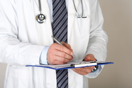 medical career: Male medicine doctor hand holding silver pen writing something on clipboard closeup. Medical care, insurance, prescription, paper work or career concept. Physician ready to examine patient and help