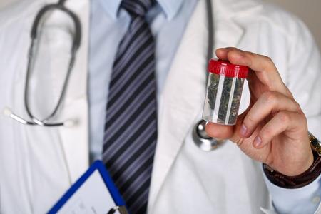 Hombre doctor en medicina explotación de la mano y ofreciendo a paciente de marihuana medicinal en el tarro. Foto de archivo