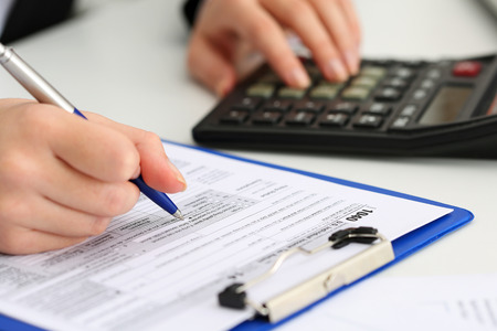 female form: Female accountant hand holding pen counting on calculator income for tax form completion closeup.