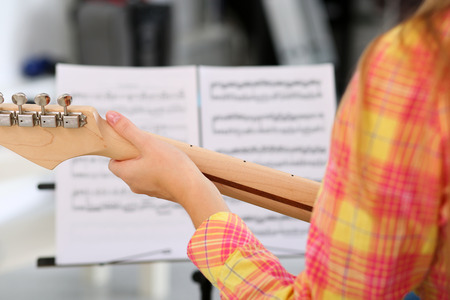 fingering: Female hand holding wooden neck of electric guitar and playing song using note papers in music stand closeup.