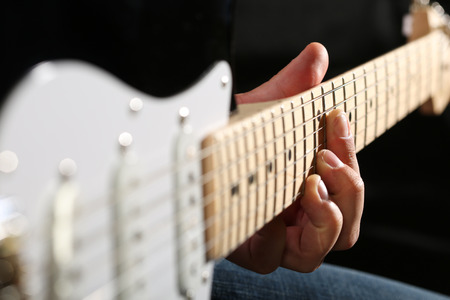 fretboard: Male hands playing electric guitar on maple fretboard closeup photo.pt Stock Photo
