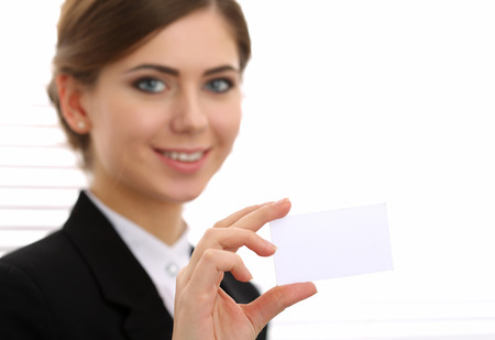 introducing: Businesswoman in suit hand holding blank calling card. Female hand showing white visiting card in camera closeup. Partners contact information exchange concept. Introducing gesture at formal meeting
