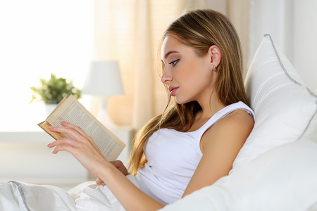 reference book: Young beautiful blonde woman lying in bed reading old book before or after sleeping. Hobby, favourite literature, reading for examination, education, work in bed, reference book concept Stock Photo