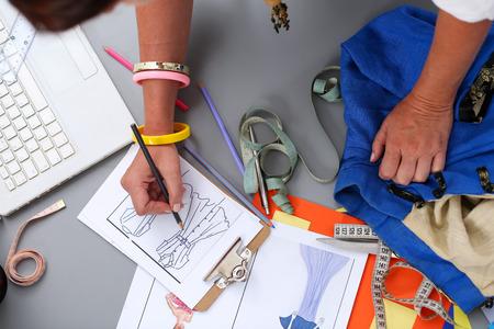 Stilista femminile mani che tengono foglio da disegno e realizzazione abbozzo della penna di vestito nuovo. Stile e progettazione sviluppo e la creazione di indumento, vestiti cucire e servizio di riparazione, sarta al concetto di lavoro