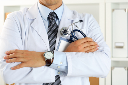 Male medicine therapeutist doctor hands crossed on his chest holding stethoscope in office closeup. Medical help or insurance concept. Physician is waiting for patient to examine