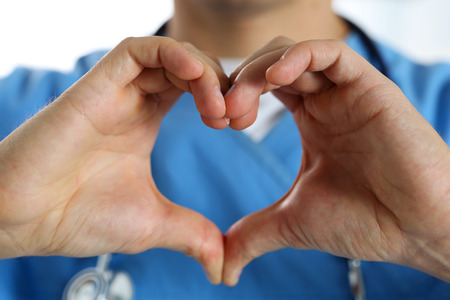 protection concept: Hands of male medicine therapeutist doctor wearing blue uniform showing heart shape closeup. Cardio prophylaxis or insurance, protection and prevention, healthy heart, eating and life style concept Stock Photo
