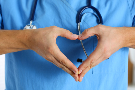 protection hands: Hands of male medicine therapeutist doctor wearing blue uniform showing heart shape closeup. Cardio prophylaxis or insurance, protection and prevention, healthy heart, eating and life style concept Stock Photo