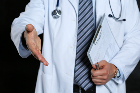 healthcare visitor: Male medicine doctor offering hand to shake closeup over black background. Greeting and welcoming friend, introduction or thanks gesture. Tests advertisement concept. Physician ready to examine patient