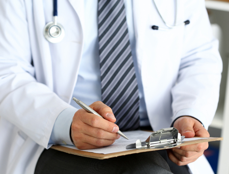 Male medicine doctor hand holding silver pen writing something on clipboard closeup. Ward round, patient visit check, medical calculation and statistics concept. Physician ready to examine patient