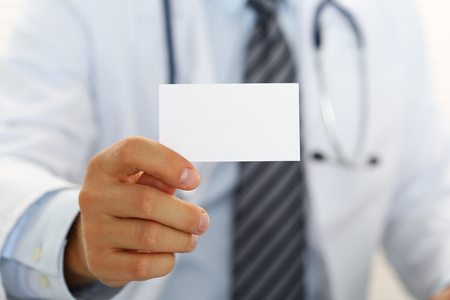 contact information: Male physician hand holding and giving white blank calling card closeup in office. Contact information exchange, introducing gesture at formal meeting, personal or family doctor concept Stock Photo