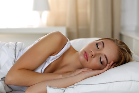 laundry concept: Young beautiful blonde woman portrait lying in bed sleeping late in the morning after hard working day tired. Fresh bedclothes, furnishing shop, new day, weekend, day off, washing or laundry concept
