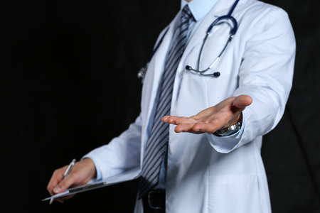 handclasp: Male medicine doctor offering helping hand closeup over black background. Friendly and cheerful gesture. Medical cure and tests advertisement concept. Physician ready to examine and save patient