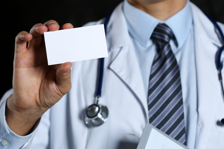 contact information: Male physician hand holding white blank calling card closeup on black background. Contact information exchange, introducing gesture at formal meeting, personal or family doctor concept