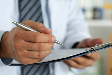 doctor writing: Male medicine doctor hand holding silver pen writing something on clipboard closeup. Ward round, patient visit check, medical calculation and statistics concept. Physician ready to examine patient