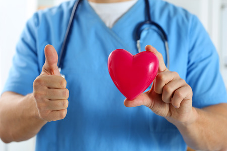 Male doctor in blue uniform hold red toy heart and show OK or approval sign with thumb up closeup. Cardio therapeutist, physician make cardiac physical, heart rate measure, arrhythmia concept Stock Photo