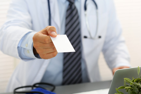 family physician: Male physician hand holding and giving white blank calling card closeup in office. Contact information exchange, introducing gesture at formal meeting, personal or family doctor concept Stock Photo