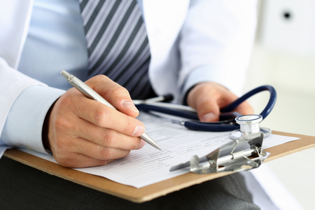 clipboard: Male medicine doctor hand holding silver pen writing something on clipboard closeup. Ward round, patient visit check, medical calculation and statistics concept. Physician ready to examine patient