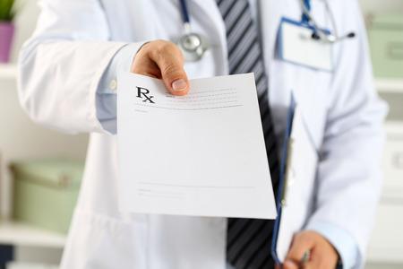 Homme docteur en médecine prise de main pad de presse-papiers et de donner à la prescription gros plan patient. Panacea et de la vie sauver, prescrire le traitement, le stockage juridique de la drogue, le concept de contraception. Formulaire vide prêt à être utilisé