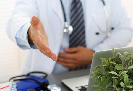 handclasp: Male medicine doctor offering hand to shake in office closeup. Greeting and welcoming friend, introduction or thanks gesture. Tests advertisement concept. Physician ready to examine patient