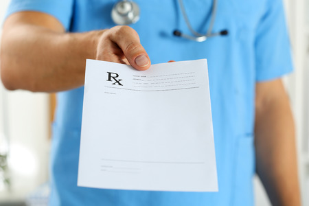 Male medicine doctor in blue uniform hold and give prescription to patient closeup. Panacea and life save, prescribe treatment, legal drug store, contraception concept. Empty form ready to be used Stock Photo
