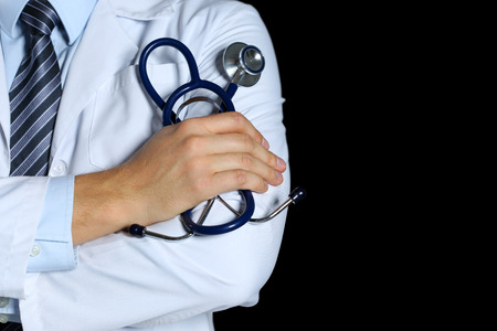 therapeutist: Male medicine therapeutist doctor hands crossed on his chest holding stethoscope in office isolated on black closeup. Medical help or insurance concept. Physician is waiting for patient to examine