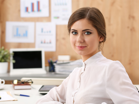 half turn: Beautiful smiling business woman sitting at office workplace half turn looking in camera portrait. Serious business and partnership, job offer, financial success, certified public accountant concept