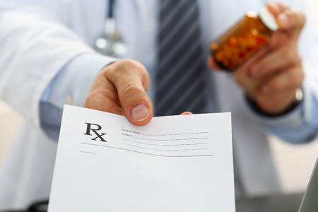 pharmacologist: Male medicine doctor hand hold jar of pills and give prescription to patient closeup. Panacea and life save, prescribe treatment, legal drug store, contraception concept. Empty form ready to be used Stock Photo