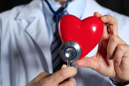 myocardium: Male medicine doctor wearing hold in hands red toy heart and stethoscope closeup black background. Cardio therapeutist, physician make cardiac physical, heart rate measure, arrhythmia concept