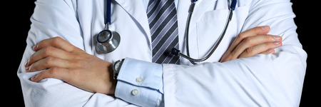 therapeutist: Male medicine therapeutist doctor hands crossed on his chest hold stethoscope isolated on black. Physical and disease prevention, examine patient, 911, instrument shop, healthy lifestyle concept