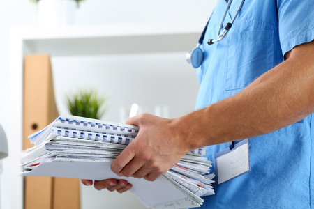 Hands of medicine therapeutist doctor wearing blue uniform holding pile of business papers at work table. Medications consumption account, bureaucracy in hospital work, patient documentation concept