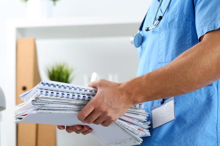 Mains de la médecine therapeutist médecin en uniforme bleu tenant pile de papiers d'affaires à la table de travail. Médicaments compte de consommation, de la bureaucratie dans le travail de l'hôpital, le concept de la documentation des patients