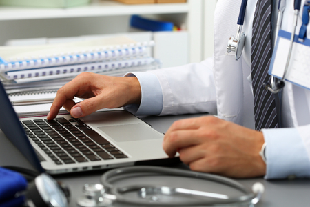 hand press: Medicine doctor hand press key on laptop computer keyboard at workplace in office. Medic instrument shop, modern communication PC, surfing, remote aid, reading news, exams preparation concept