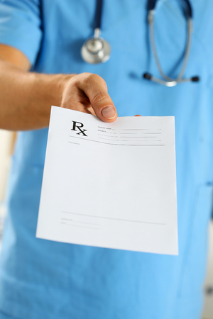pharmacologist: Male medicine doctor in blue uniform hold and give prescription to patient closeup. Panacea and life save, prescribe treatment, legal drug store, contraception concept. Empty form ready to be used Stock Photo