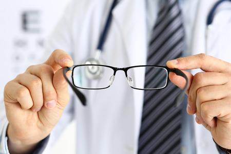 shortsightedness: Male medicine doctor hands giving pair of black glasses to patient. Eyesight test and correction, excellent vision, laser surgery alternative, driver health certificate examination concept