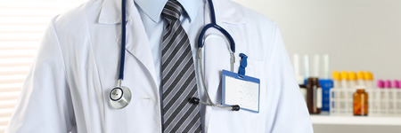 therapeutist: Stethoscope lying on male therapeutist doctor chest wearing necktie. Medical care, help or insurance, equipment shop or store concept. Physician waiting for patient to examine. Letterbox view